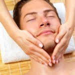 Close up of a man receiving facial massage from a woman, while on holiday at the beauty spa